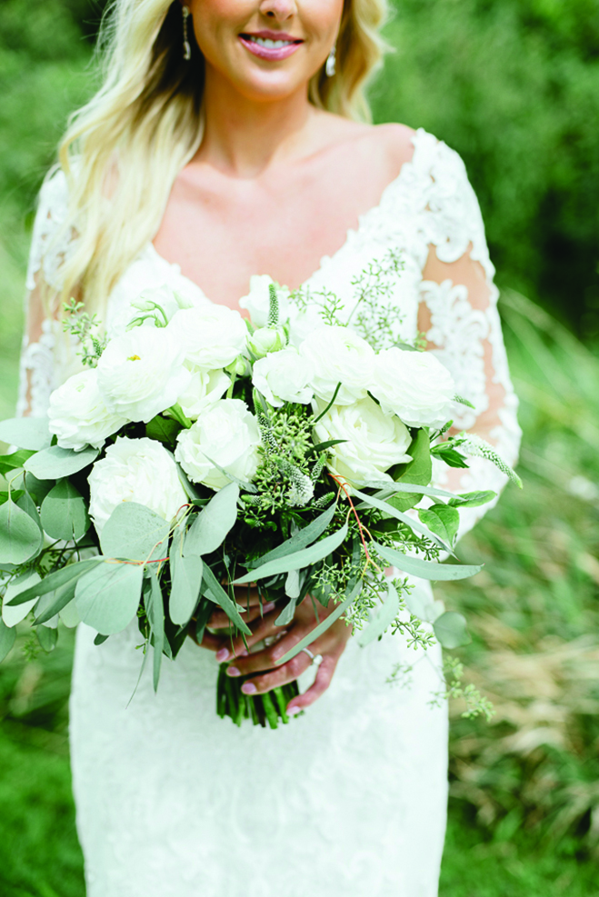 Chelsey holds her white wedding bouquet at Round Lake Vineyards & Winery
