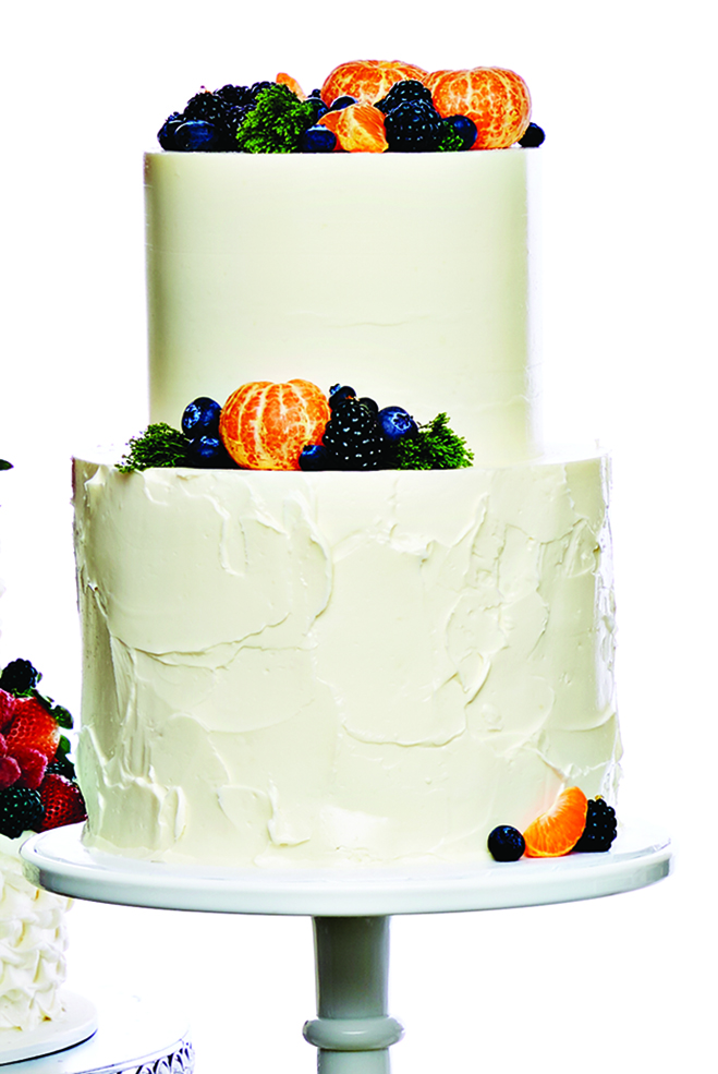 A buttercream tiered cake with clementines, blueberries and blackberries from Farina Baking Co.