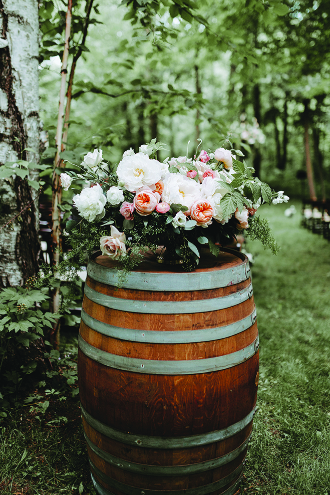 Flowers in a barrel at Kate and Lucas' wedding at Creekside Farm Weddings & Events