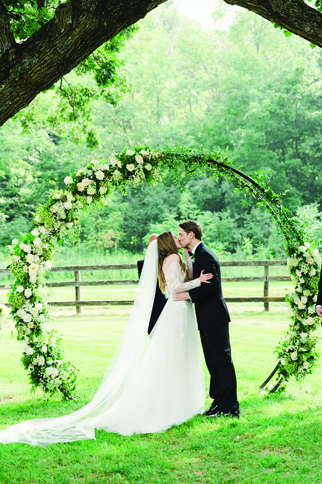 Laura and Rob kiss under a round arch at Mayowood Stone Barn