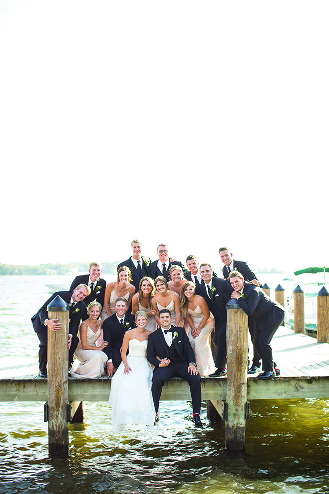 Paige, Jake and their wedding party sit on a dock at the Wayzata Country Club