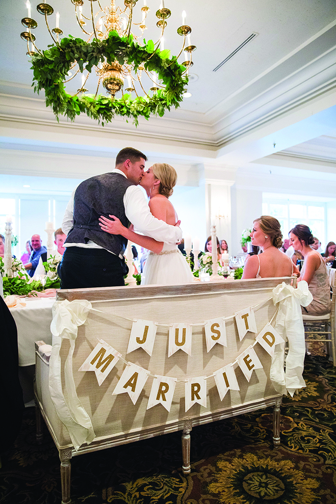 "Paige and Jake kiss in front of a ""Just Married"" sign at their wedding reception at the Wayzata Country Club"