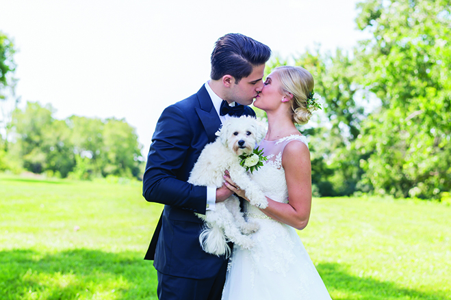 Taylor and John hold their dog while kissing.