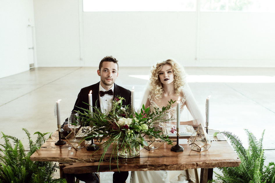 A sweetheart table full of greenery with ivory, gold and white decor. The bride and groom sit together.
