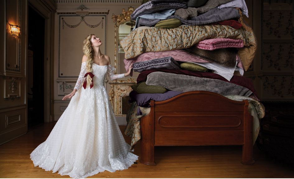 "In ""Princess and the Pea"" style, the bride, in a lacy off-the-shoulder gown, contemplates a bed piled high with mattresses."