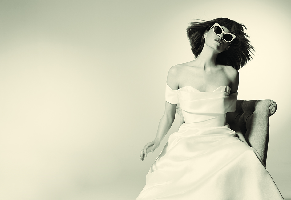 A minimalist gown silhouette, cat-eye sunglasses and a blunt bob adorn this bride
