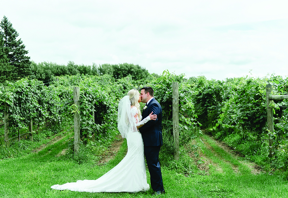 Tom and Chelsey kiss on their wedding day at Round Lake Vineyards & Winery