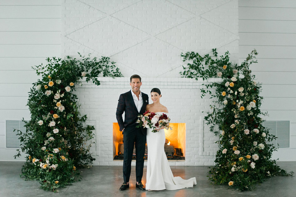Sydney and Casey pose before the beautiful fireplace and their rosy floral installation at Hutton House