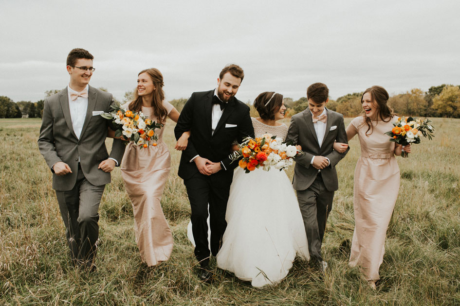 The bridal party, in shades of orange and pastel pink, walks through a rolling field