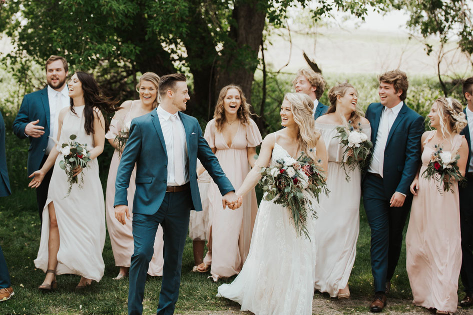 The pastel bridal party walks through the fields at Stonewall Farms in Willmar.