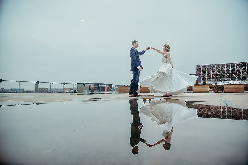 Bride and groom dance over a reflective puddle on the rooftop of A'BULAE.