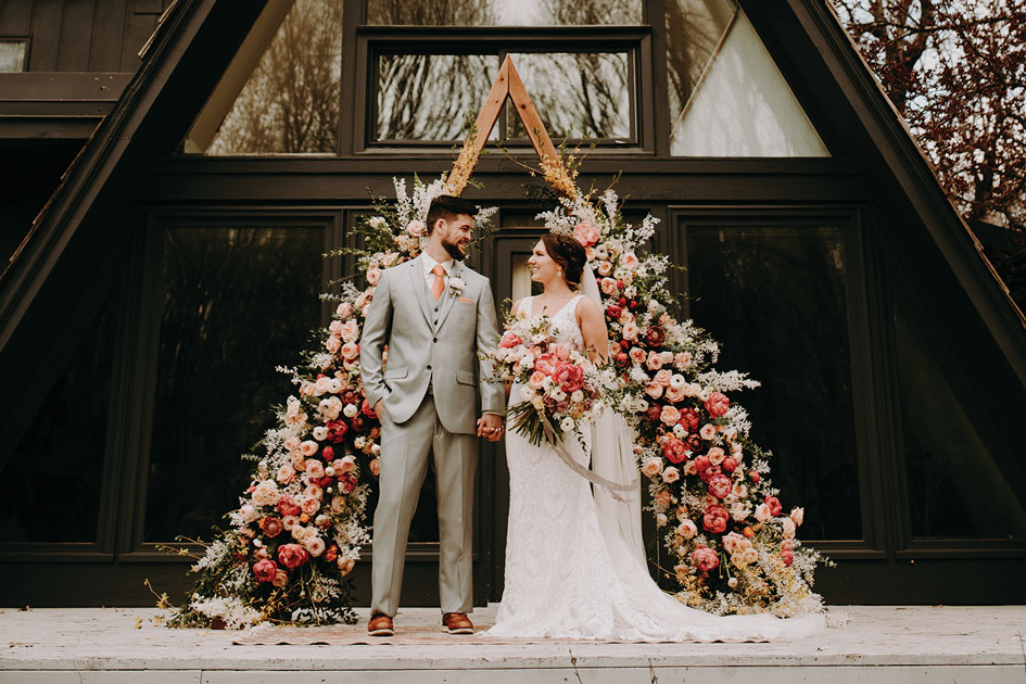 A lush floral arch serves as a ceremony backdrop at Grey Cloud House.