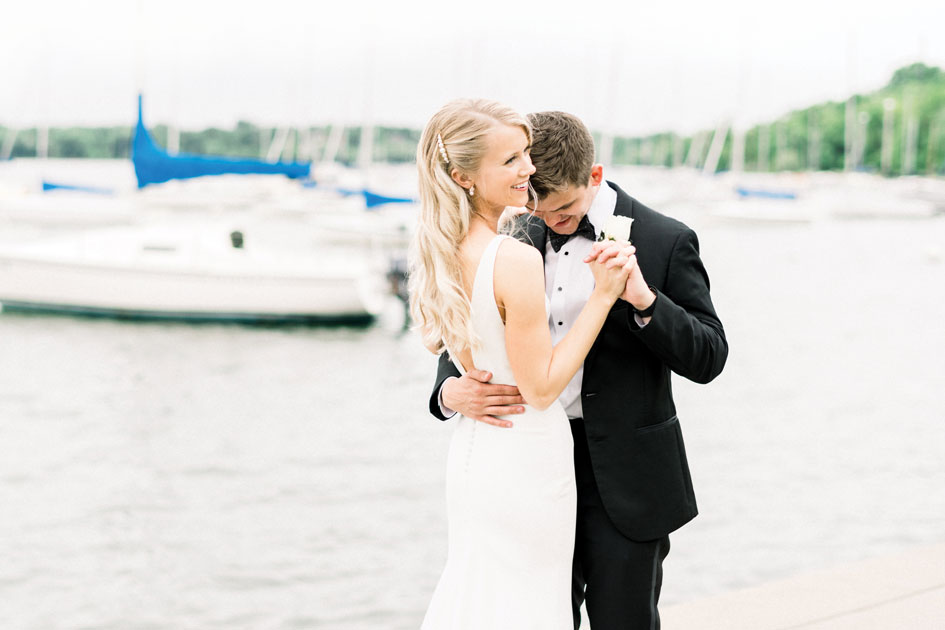 A bride and groom on a lake at their first dance.