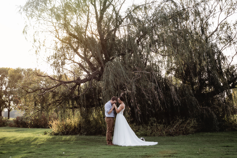 Newlyweds Haley and Alex in front of a willow tree at Green Lake Bible Camp