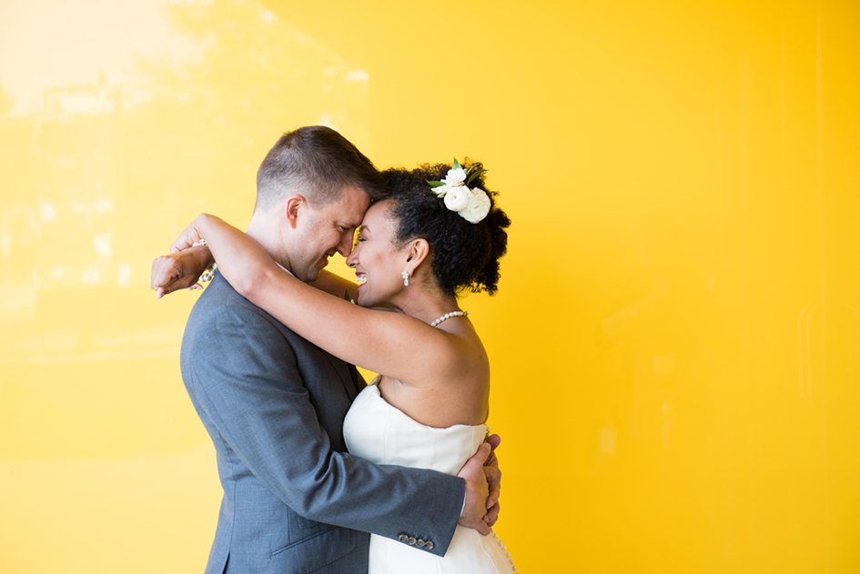 Newlywed couple happily hugging in front of a bright yellow accent wall at Walker Art Center.