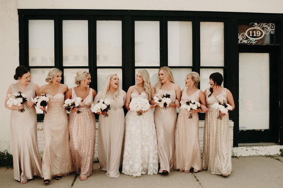 The bride squad, wearing neutrals, walks through Minneapolis.