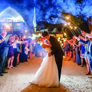 Family and friends hold sparklers as Taylor and John kiss as their wedding day at Historic John P. Furber Farm ends.