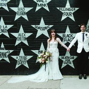 Sarah and Scott pose for a wedding photo in front of First Avenue.