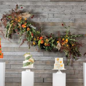 A playful installation of ranunculus, roses, olive branches and ferns frolics across the wall behind an array of autumn-inspired cakes at Machine Shop.