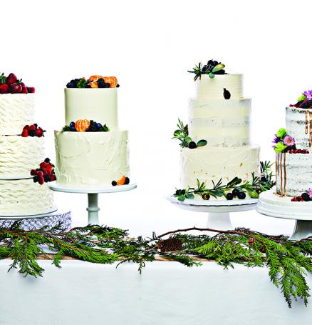 Three tiered, buttercream wedding cakes with fruit.