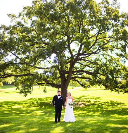 Jake and Paige hold hands in front of a tree during their wedding at the Wayzata Country Club,