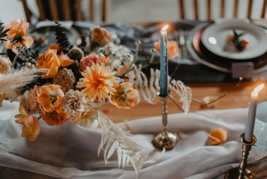 Orange blooms bedeck a table with blue tapers and flowing linen