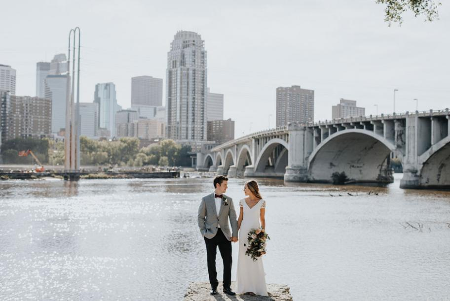 Kelsey and Grant stand before the Stone Arch Bridge