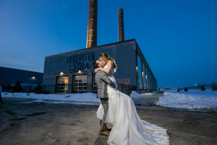 Newlyweds kissing outside of Northern Stacks wedding venue.