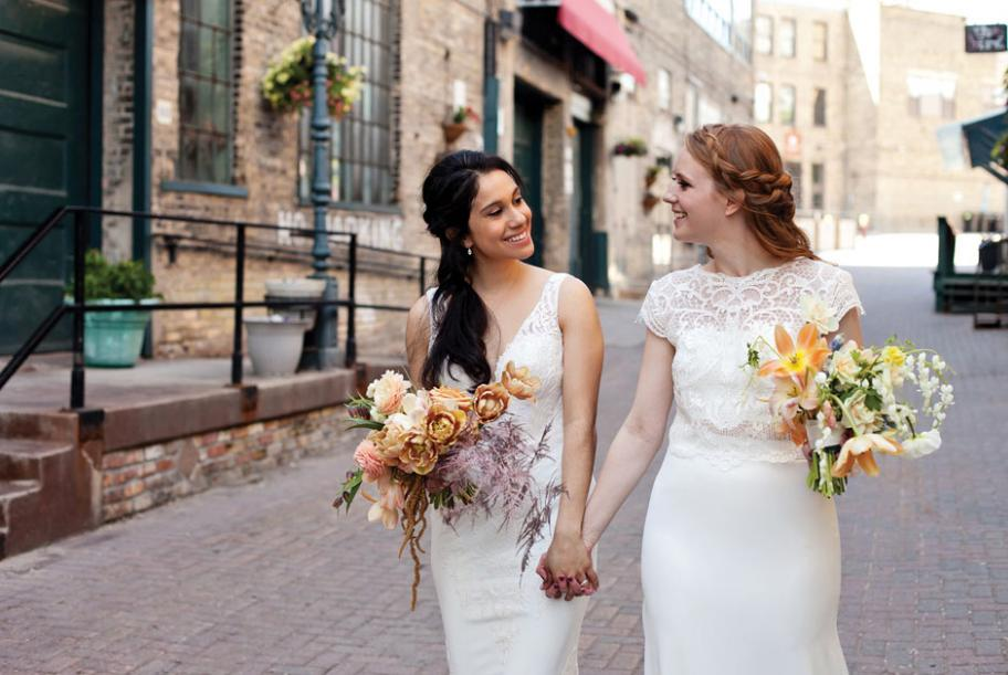 Newlyweds Sophia and Lindsay strolling down the street with bouquets.