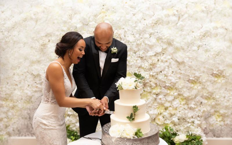 The bride cuts the cake with the groom (former Minnesota Vikings player Michael Floyd).